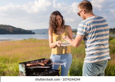Man and woman grilling bratwurst at lakeside in nature