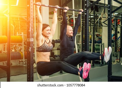 man and woman in the gym teamwork hang on the bar and strengthen the abdominal muscles and back