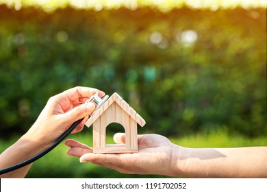 Man and woman hand holding a home and using stethoscope show inspection or check the financial condition in the public park for buy a new real estate or a new home concept.