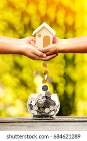 Man and woman hand holding new house for family and coin drop in the jar in the public park, Saving money for real estate to buying a new home and loan for asset management for investment concept.