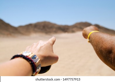 Man and woman hand pointed on direct way to a desert dunes and mountains.Travel destination adventure.Empty space for advertising text.Close up travel footage