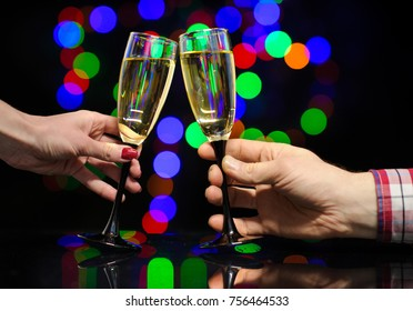 Man and woman hands with full champagne glasses. Cheers