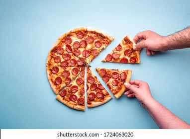 Man and woman hands grabbing pizza slices. Sliced pepperoni pizza on a blue background, above view. Top view with delicious pepperoni pizza.