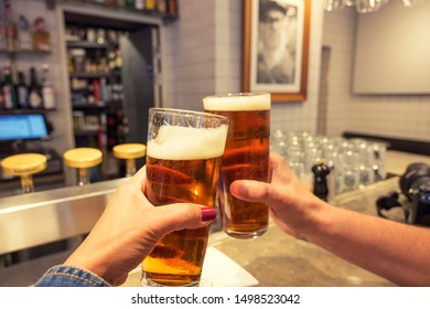 Man and woman hands holding beers cheers to each other in the bar background