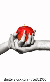 Man and woman hands holding forbidden fruit of sin, red apple, black and white selective coloring, isolated