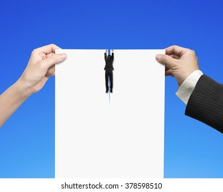 Man and woman hands holding the tearing contract blank white paper with businessman hanging on it, isolated on blue.