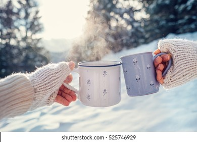 Man and woman hands in knitting mittens with cups of hot tea on winter forest glade
