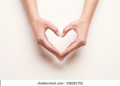 man and woman hands shows heart gesture on light grey background.