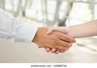 Man and woman  handshake isolated on business background