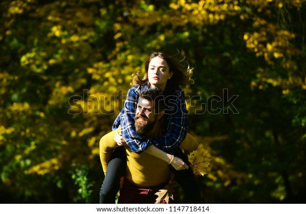 Man and woman with happy faces on natural background. Girl and bearded guy or happy lovers have fun outdoors having piggyback ride. Couple in love walks in autumn park. Freedom and fall season concept