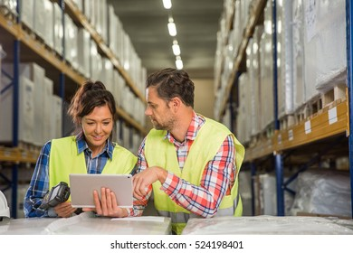 Man and a woman have short meeting in a warehouse on checking inventory levels of goods. First in first out, Last in last out, team working together concept photo.