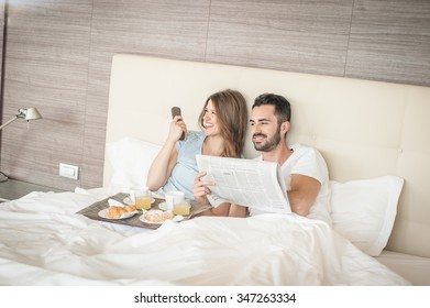 A man and a woman are having breakfast on the bed.