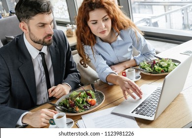 Man and woman having business lunch at restaurant sitting at table eating salad drinking hot coffee browsing laptop concentrated serious