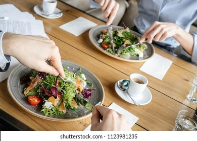 Man and woman having business lunch at restaurant sitting at table eating two plates of fresh vegetable salad close-up