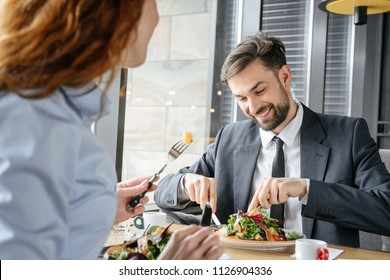 Man and woman having business lunch at restaurant sitting at table businessman eating fresh salad concentrated smiling happy holding fork and knife businesswoman close-up