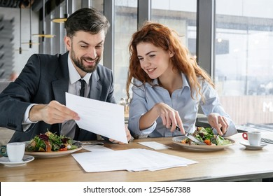 Man and woman having business lunch at restaurant sitting at table eating fresh salad guy showing his collegue document conditions smiling happy