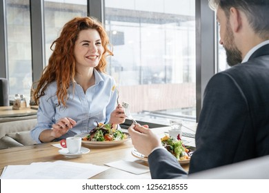 Man and woman having business lunch at restaurant sitting at table eating fresh salad drinking hot espresso talking smiling cheerful