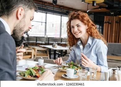 Man and woman having business lunch at restaurant sitting at table businessman eating vegetable salad with feta cheese and salmon concentrated businesswoman laughing joyful