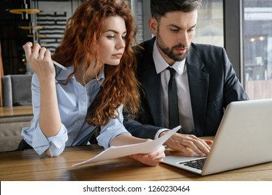 Man and woman having business lunch at restaurant sitting at table working on laptop concentrated holding documents