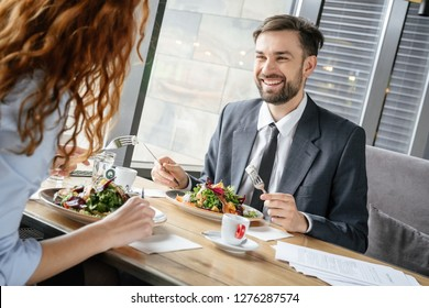 Man and woman having business lunch at restaurant sitting at table eating healthy salad discussing work smiling joyful