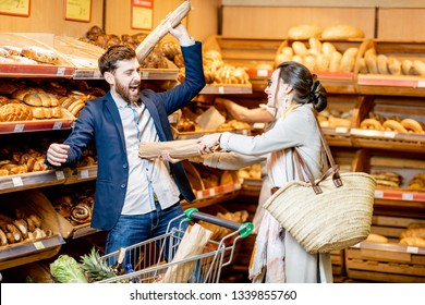 Man and woman having fun fighting with baguettes while shopping food in the supermarket