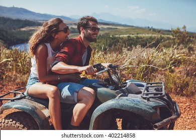 Man and woman having fun on an off road adventure. Couple riding on a quad bike in countryside on a summer day.