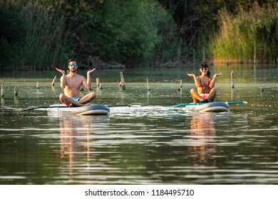 Man woman having fun paddleboarding on lake. Male and female tourists during summer vacation.