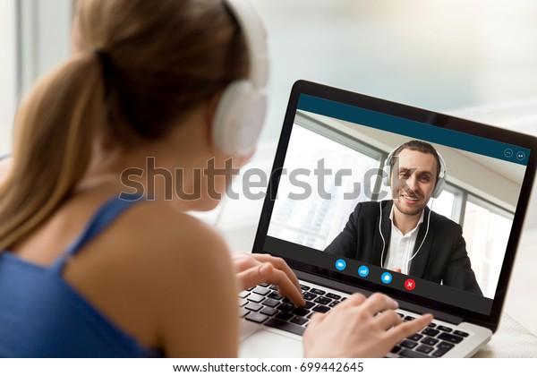 Hombre y mujer con auriculares que se comunican en línea mediante videollamadas, mirando la ventana de la aplicación de videoconferencia de pantalla completa, videochat con cámara web, citas virtuales, relaciones de larga distancia, vista posterior cerrada