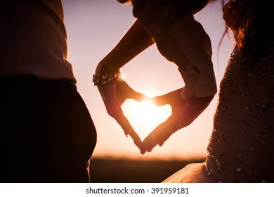 man and woman with the help of their hands joined fingers heart symbol and mutual undying love against the backdrop of a beautiful sunset