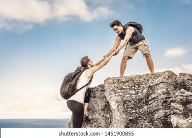 Man, woman helping each other climb up mountain. Teamwork, and challenging yourself concept.