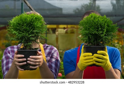 Man and woman hiding behind trees