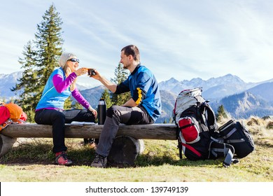 Man and woman, hikers camping in mountains. Young couple drinking and planning trip.