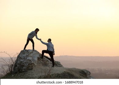 Man and woman hikers helping each other to climb stone at sunset in mountains. Couple climbing on high rock in evening nature. Tourism, traveling and healthy lifestyle concept.