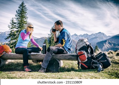 Man and woman hikers hiking and drinking in mountains. Young couple looking at map and planning trip or get lost. Vintage style trekking and recreation concept