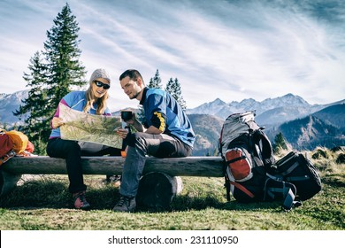 Man and woman hikers hiking in mountains. Young couple camping, looking at map and planning trip or get lost. Getting rest and drinking coffee or tea, navigation and looking for direction