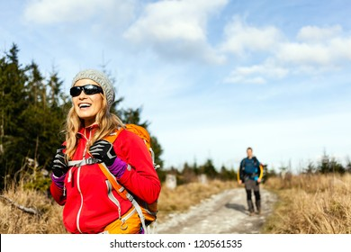 Man and woman hikers hiking on mountain trail autumn or winter nature. Young couple backpackers walking in forest, Poland.