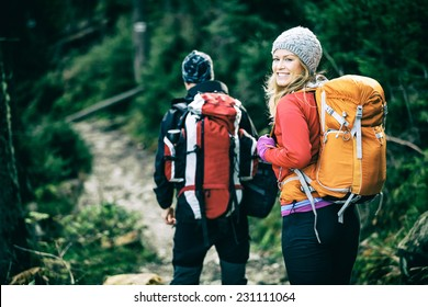 Man and woman hikers trekking in mountains. Young couple walking with backpacks in forest, Tatras in Poland. Old vintage photo style.