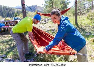 Man and woman in hiking equipment setting up a hammock between trees at the top of the mountain.