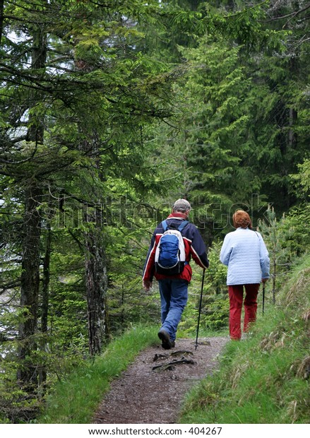 man and woman hiking on mountain lake footpath in Austria