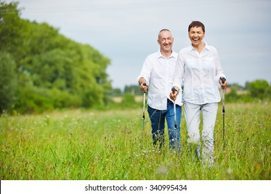 Man and woman hiking in summer over a meadow with walking sticks