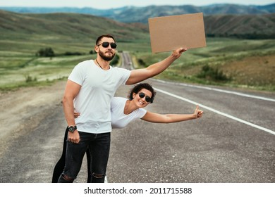 A man and a woman are hitchhiking. Wanderlust, autostop journey concept. Young people traveling hitchhiking. Tourists catches car on road. Hitchhiking couple on the road. Copy space