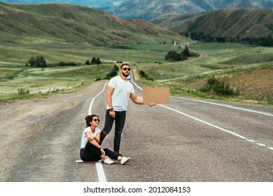 A man and a woman are hitchhiking. Wanderlust, autostop journey concept. Young people traveling hitchhiking. Hitchhiking couple on the road. Hitchhiking trip. Car travel. Two by the road. Copy space