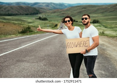 A man and a woman are hitchhiking. A young couple goes hitchhiking around the country. Free hitchhiking trip. A lover who travels free by hitchhiking. The couple goes traveling. Couple by the road