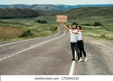 A man and a woman are hitchhiking. A young couple goes hitchhiking around the country. Free hitchhiking trip. A lover who travels free by hitchhiking. The couple goes traveling. Copy space
