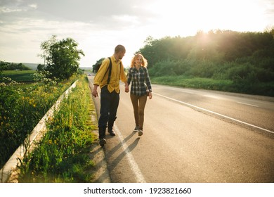 A man and a woman are hitchhiking. A young couple goes hitchhiking around the country. Free hitchhiking trip. A lover who travels free by hitchhiking. The couple goes traveling. Couple by the road.