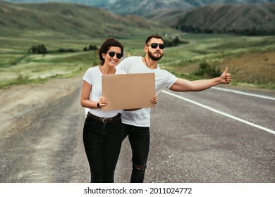 A man and a woman are hitchhiking. A young couple goes hitchhiking around the country. Free hitchhiking trip. A lover who travels free by hitchhiking. The concept of travel. Copy space