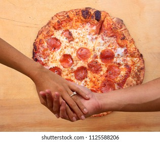 Man and Woman hold hands with pizza background. I love you more than pizza. Romance and love stronger than love for pizza.