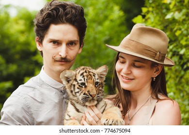 A man and woman hold tiger cub
