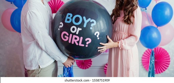 "man and woman holding black balloon with ""boy or girl?"" on gender reveal party"