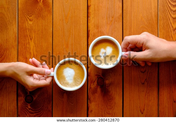 Man and woman holding a cup of coffee in the cafe